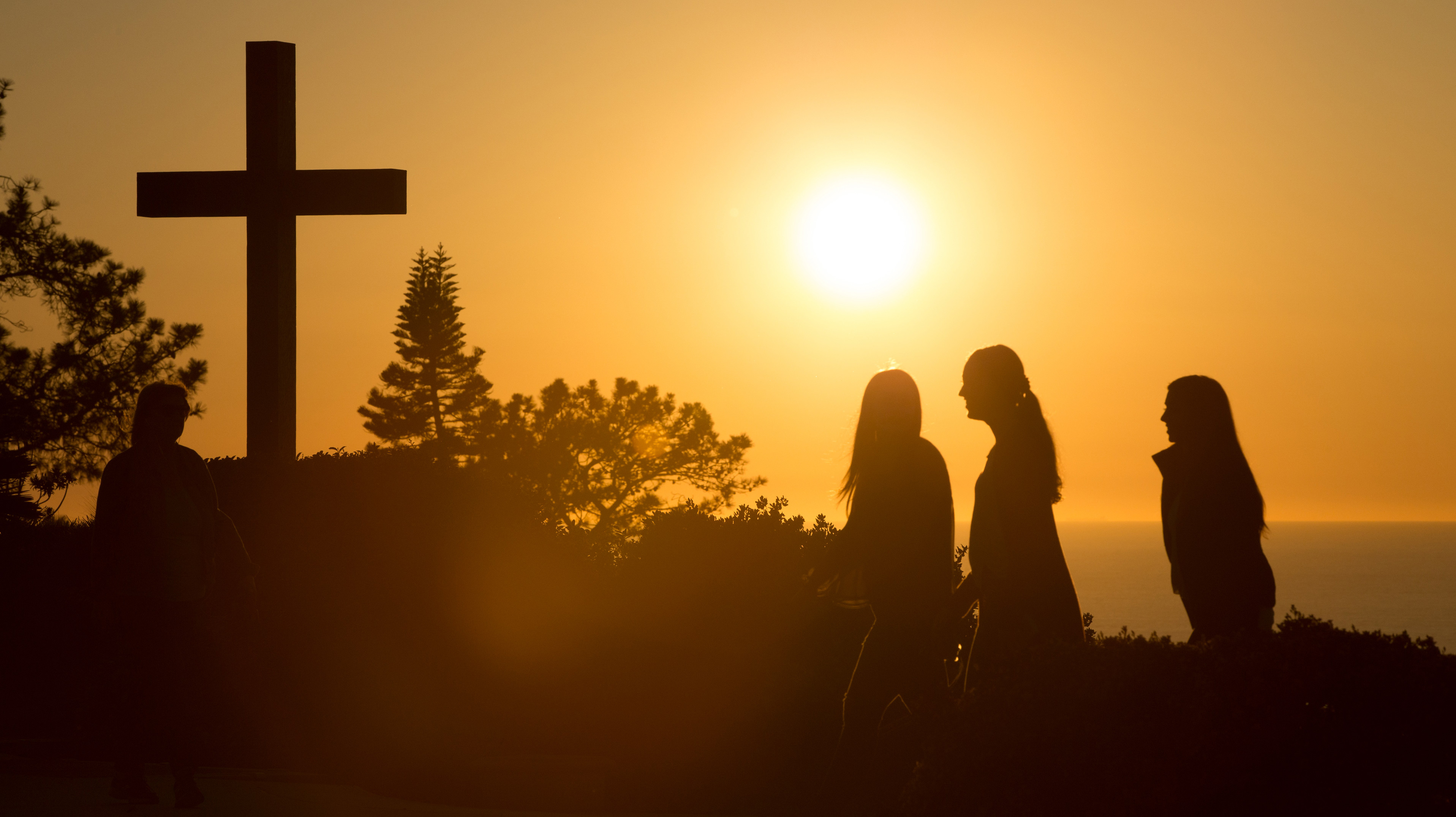 Students walk past the cross on PLNU campus during sunset