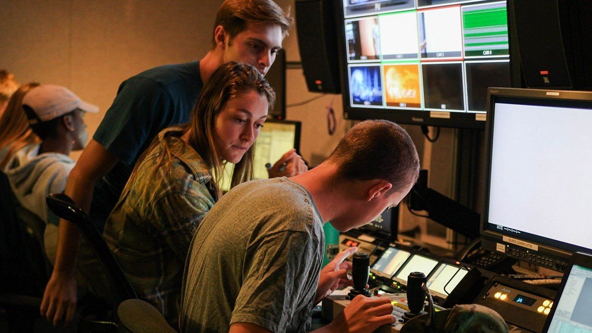 A group of Media Comm students work behind the scenes production in the PointTV studio