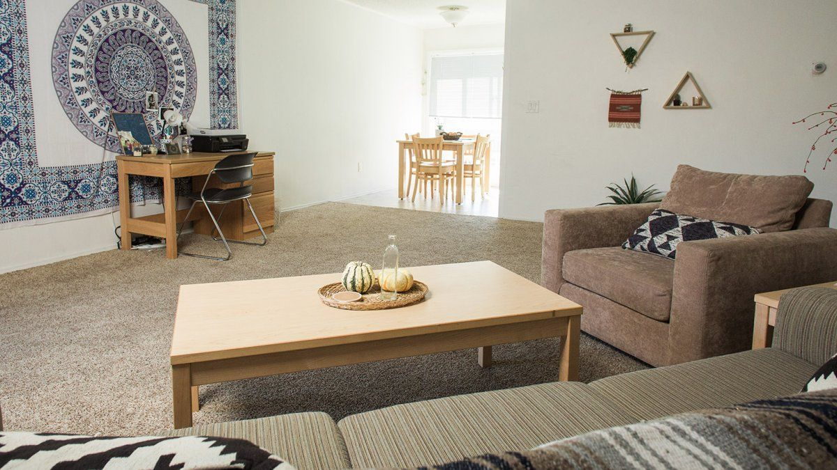 A Colony Apartment Living Room With Multiple Couches Desk And Open Space