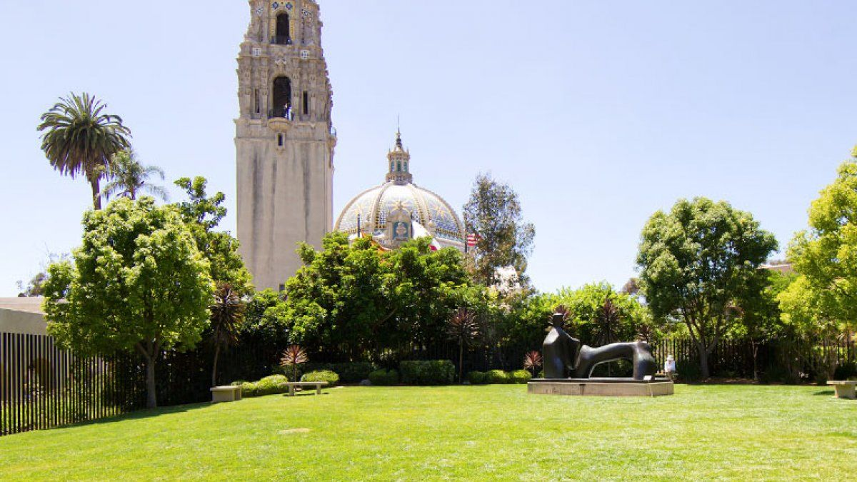 The California tower and dome rise above a grassy lawn in Balboa Park on a sunny day