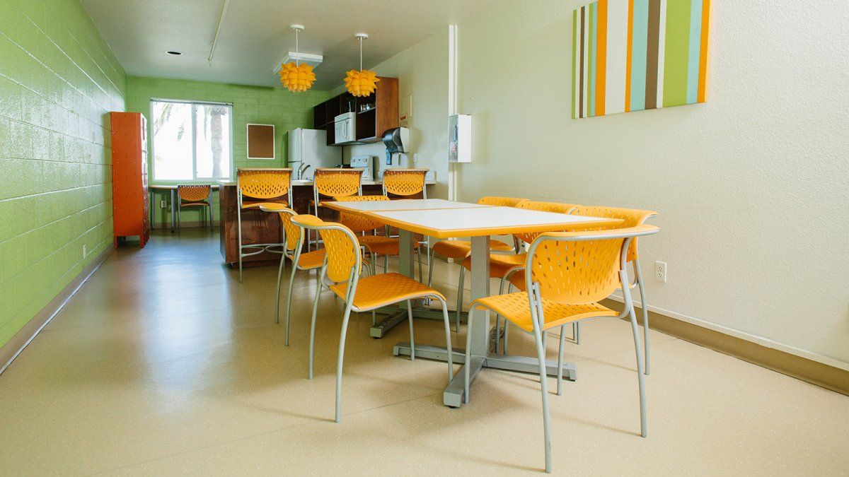 Finch's shared kitchen space is a colorful contrast of tables, chairs, and artwork on the walls.