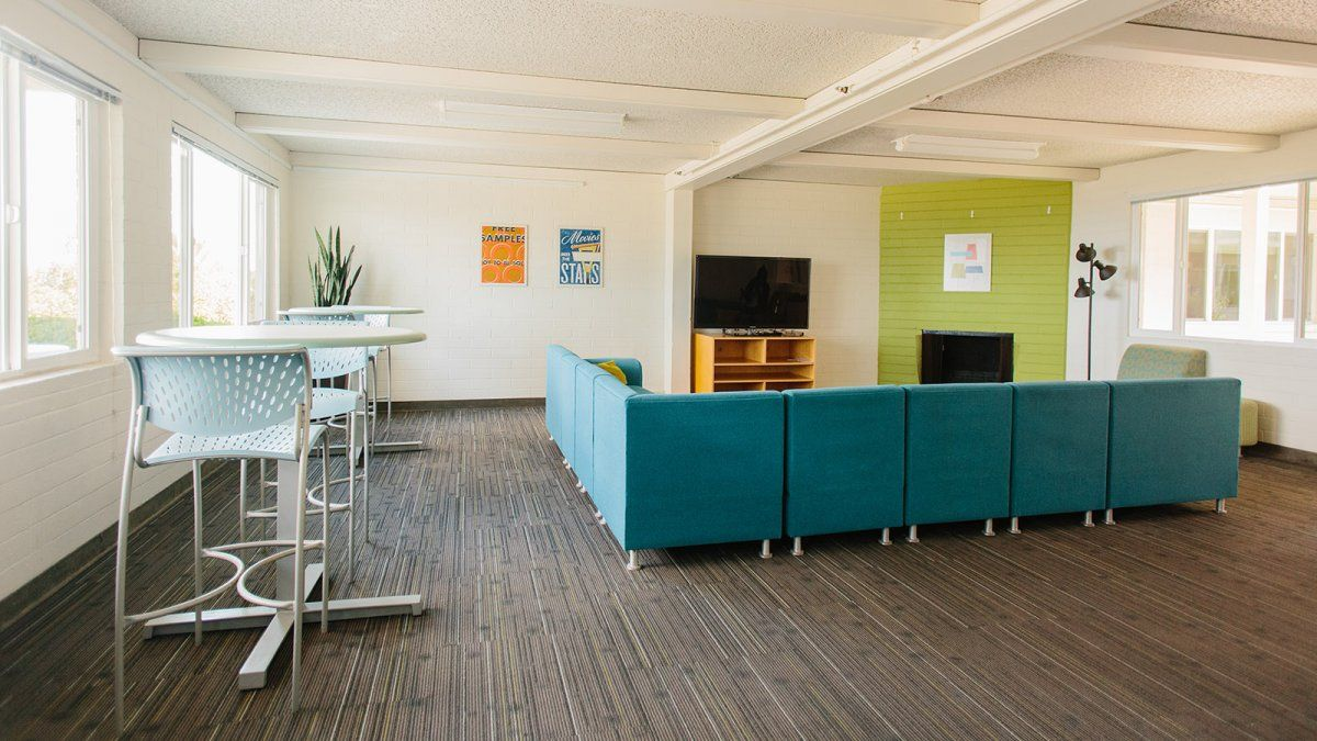 The green and teal lounge space of Finch Hall with TV, couches, and smaller tables.