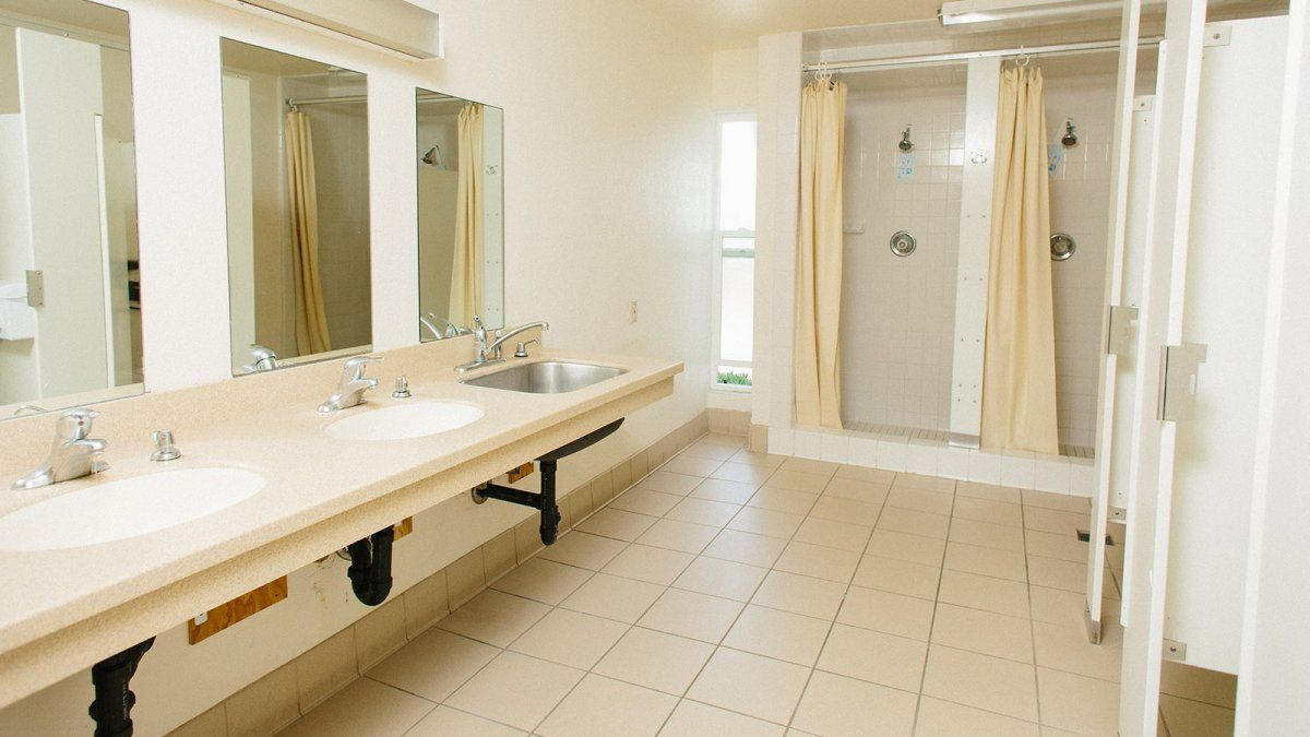 Large bathroom space with multiple shower stalls, sinks, and toilets.