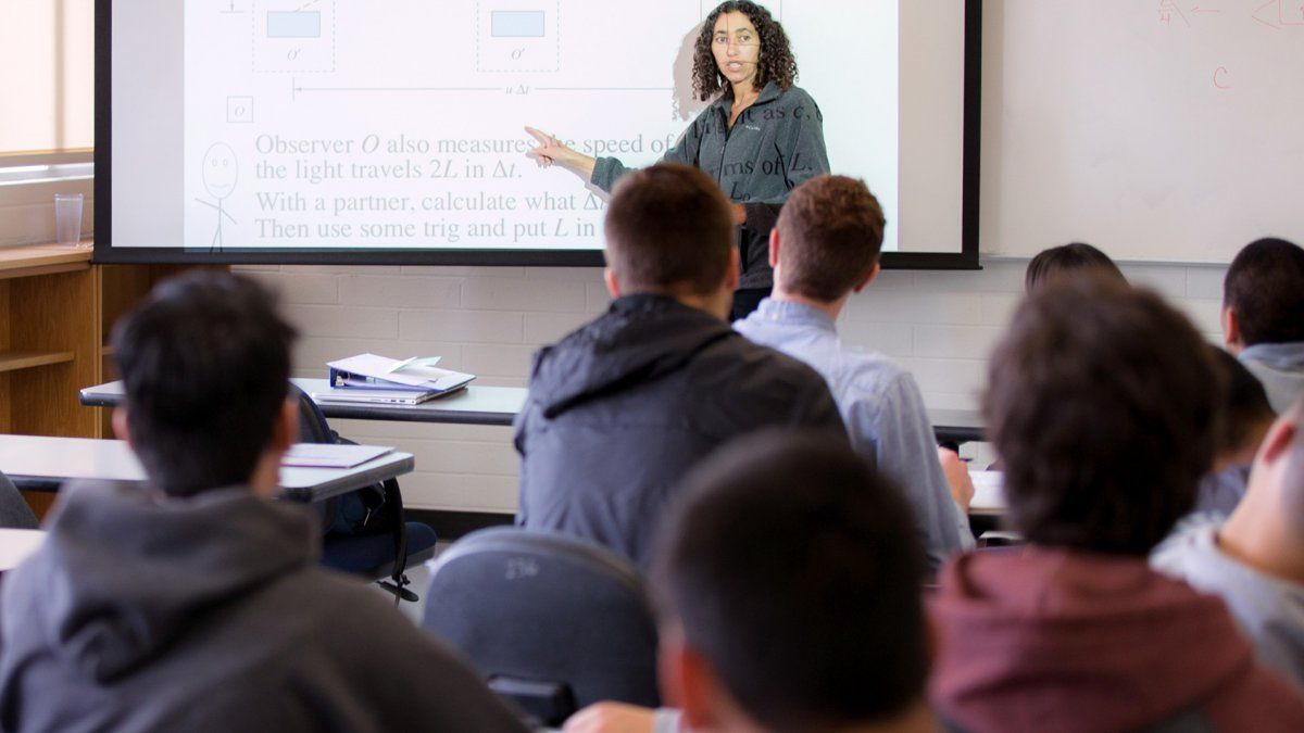 A professor teaches her class using a projector screen.