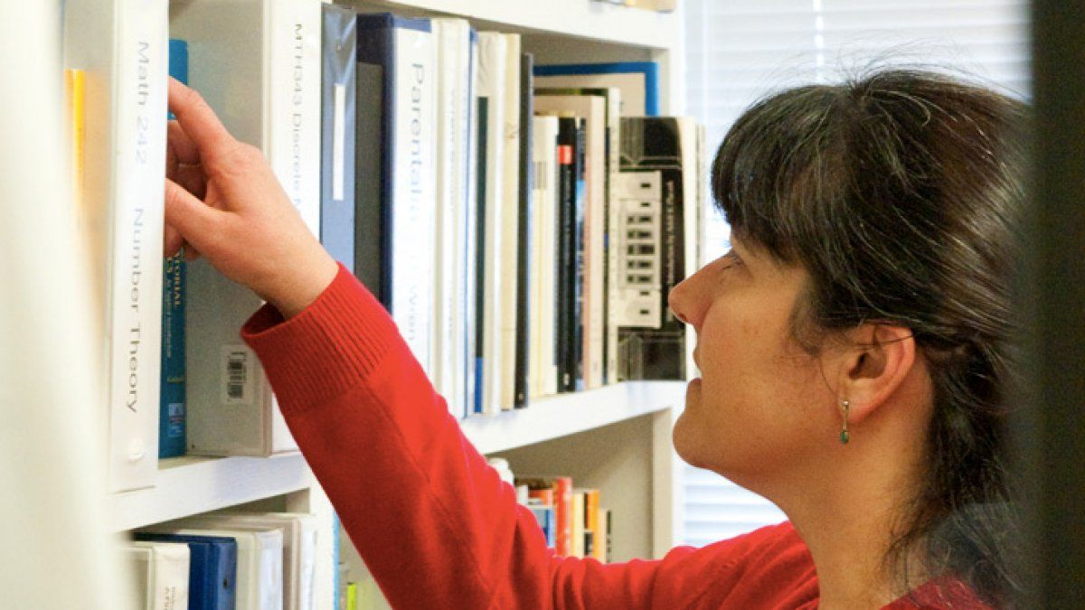 Maria Zack reaches for a book in her office bookcase.