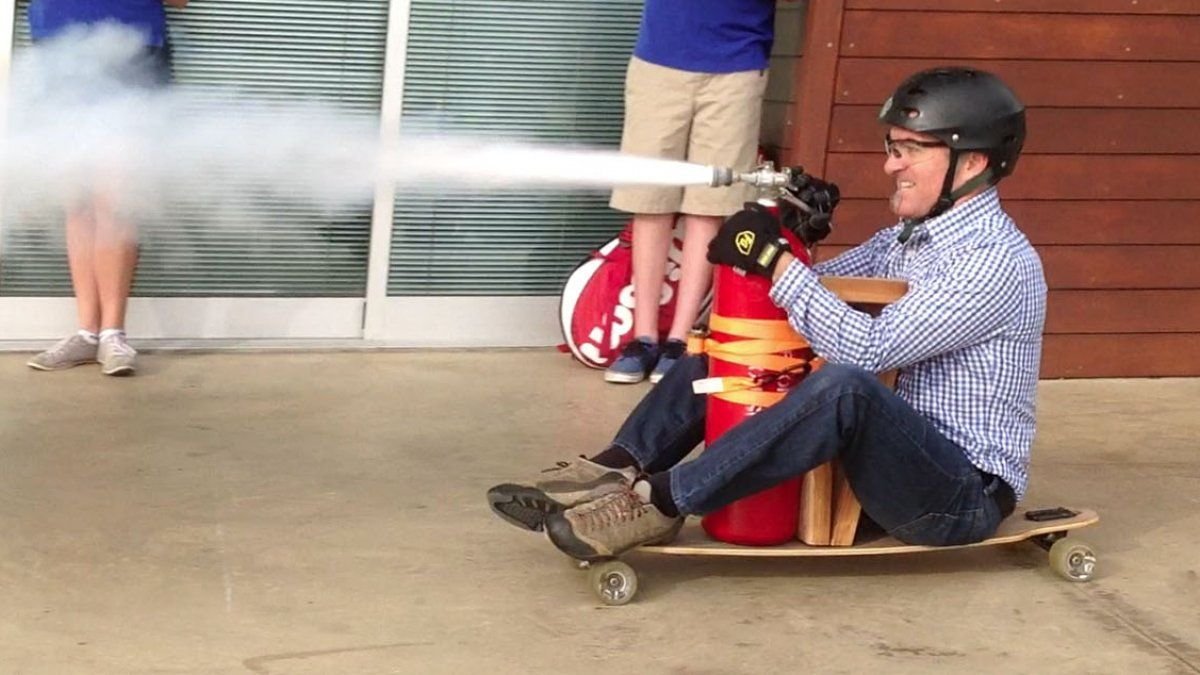 Myles Vandergrift conducting an experiment seated on a skateboard, wearing a helmet, with a fire extinguisher taped to the skateboard spewing its contents to propel the skateboard forward