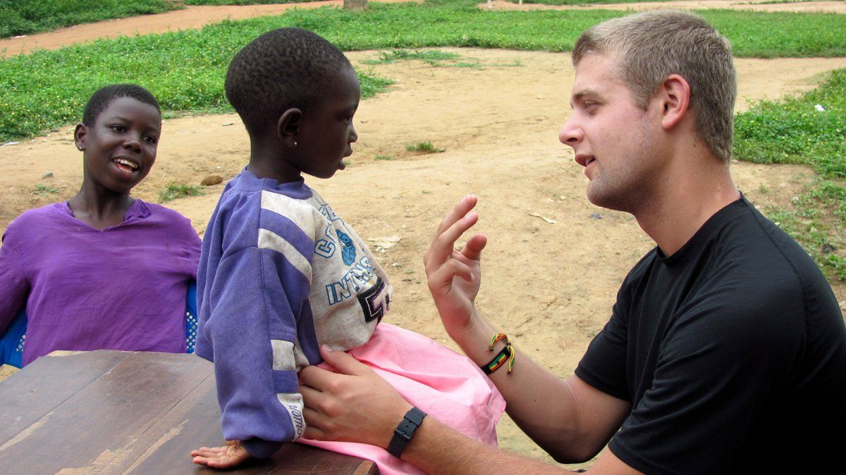 A PLNU student talks with a young girl in Ghana during a medical Loveworks trip.