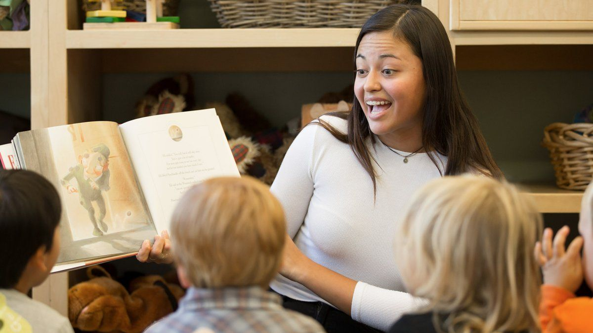 A teacher reads a picture book out loud to a group of small children