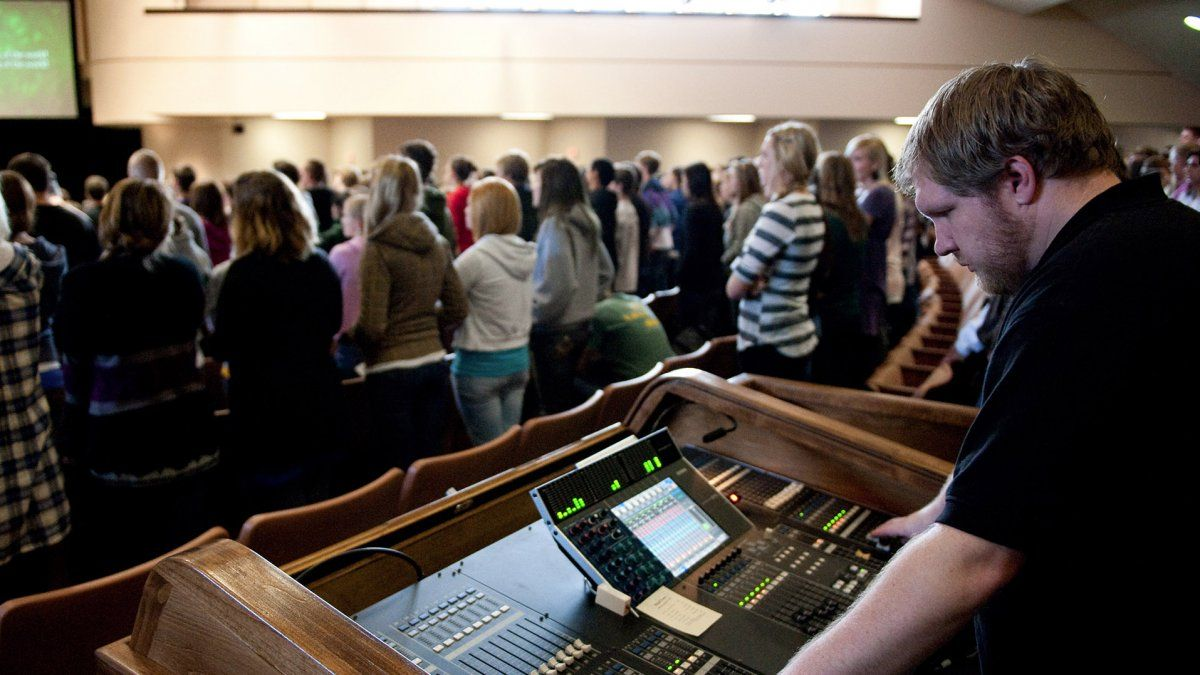 A student technician uses his talents monitoring sound levels to worship during chapel.