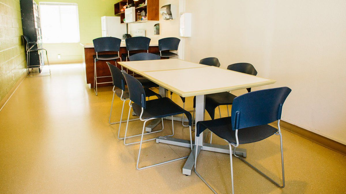 The kitchen space in Wiley, with multiple tables, chairs, and lockers for food storage.