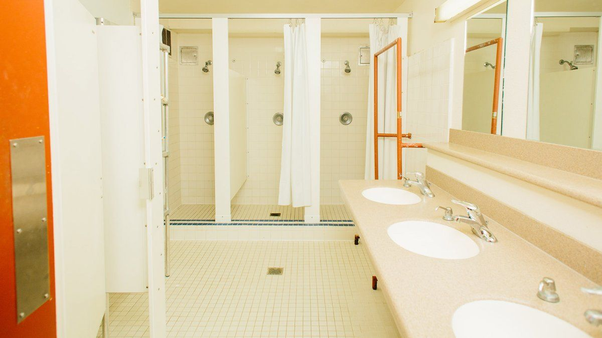 3 Individual Shower Stalls In A Young Hall Bathroom