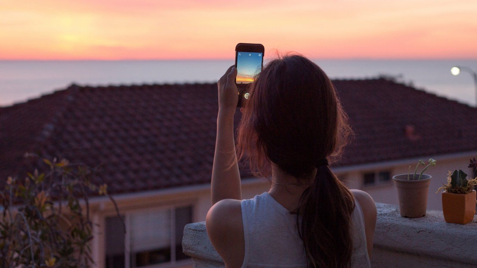 A female student takes a photo of sunset on her iPhone from her Flex apartment