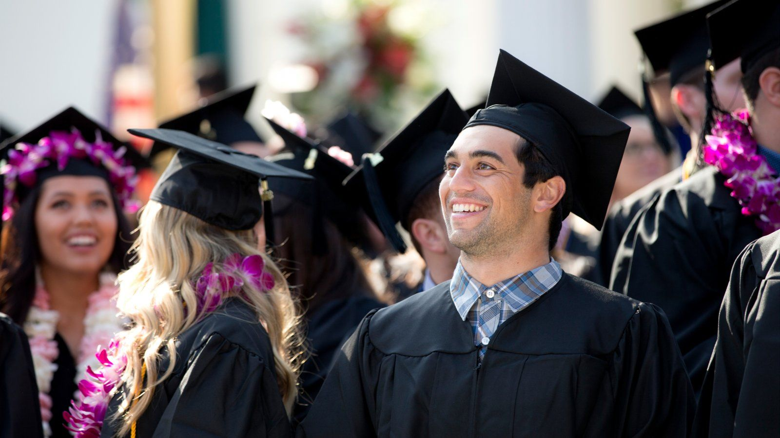 Male graduate student during commencement in crowd