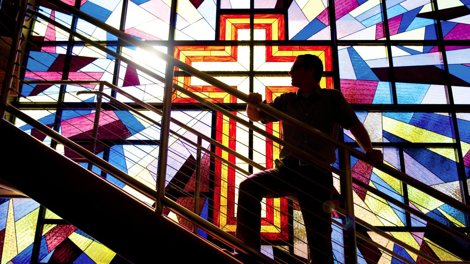 Man climbs staircase in shadow, backlit by sun coming through giant stained glass window of a cross