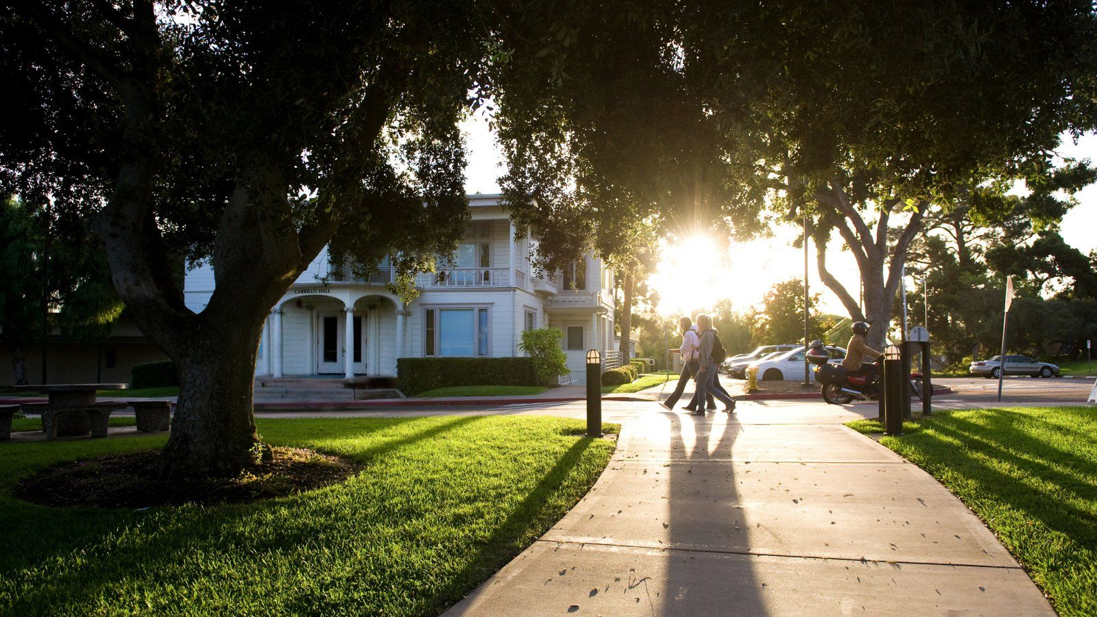 Students walk past Cabrillo Hall with the sun in the background.