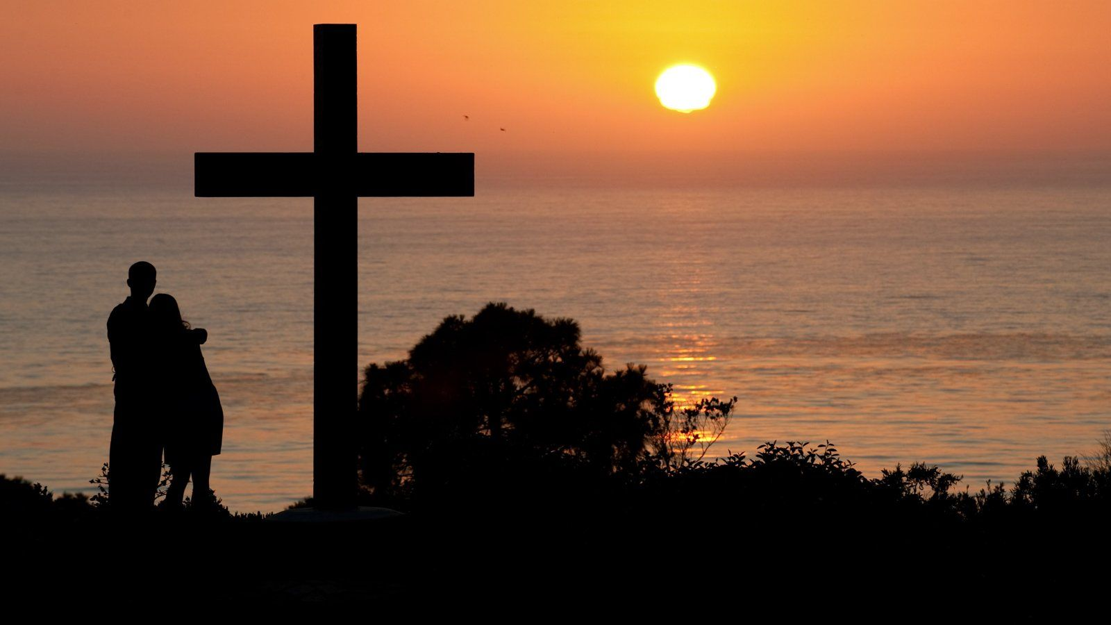 Two students watch the sunset over the Pacific Ocean from the cross on PLNU's campus