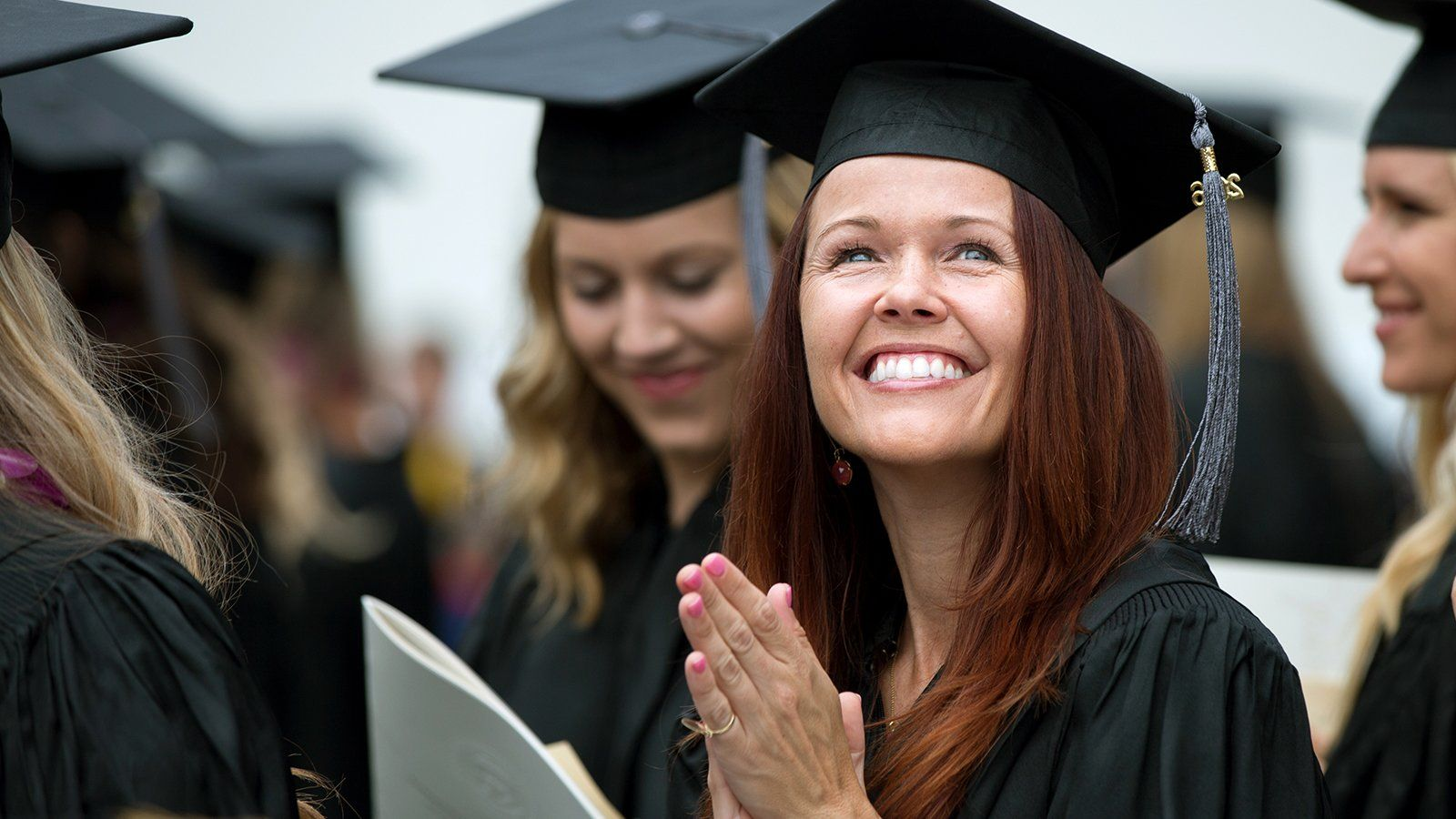 A female graduate student smiles up at her friends and family during commencement.
