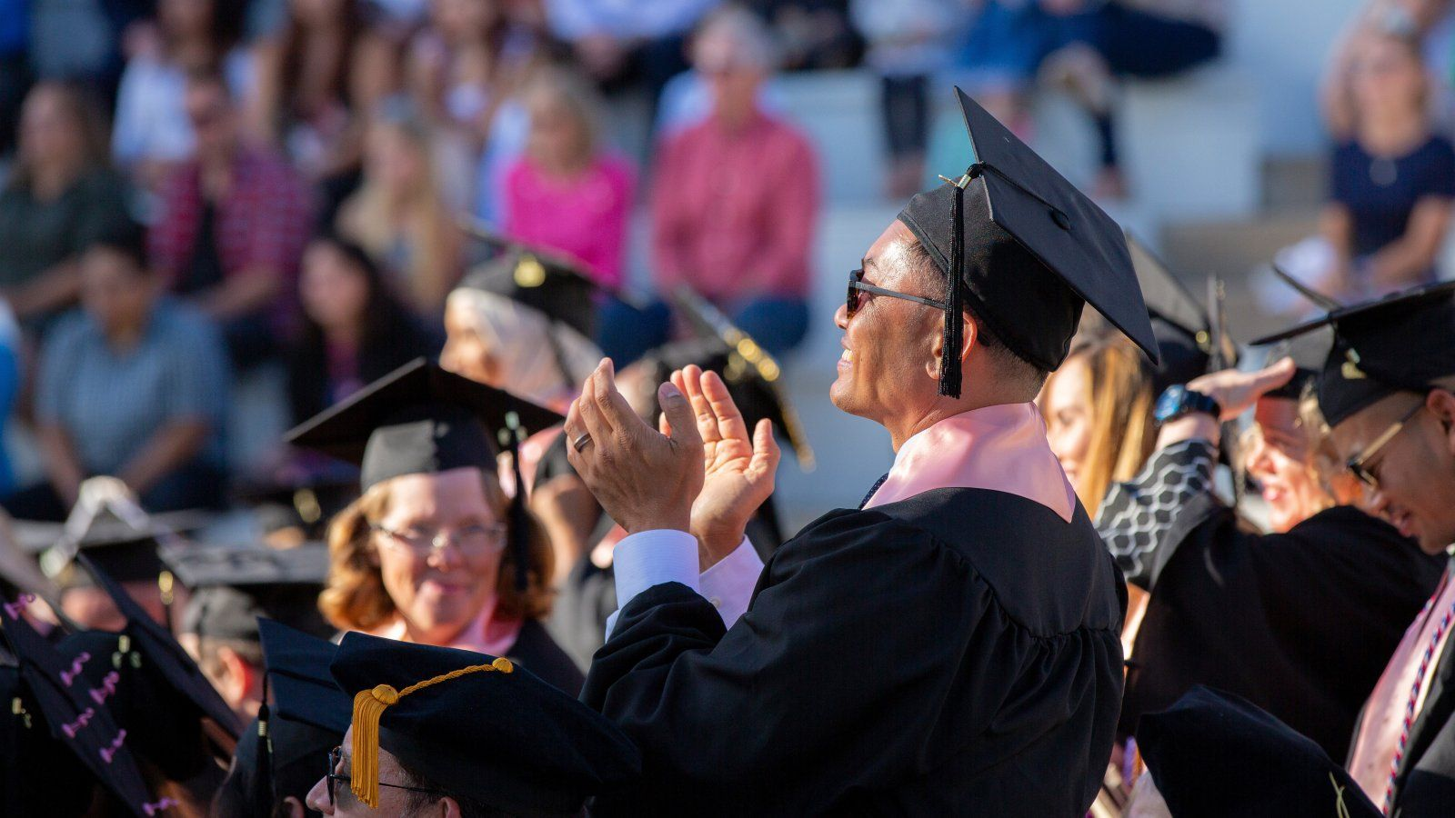 Male graduate student applauding during commencement