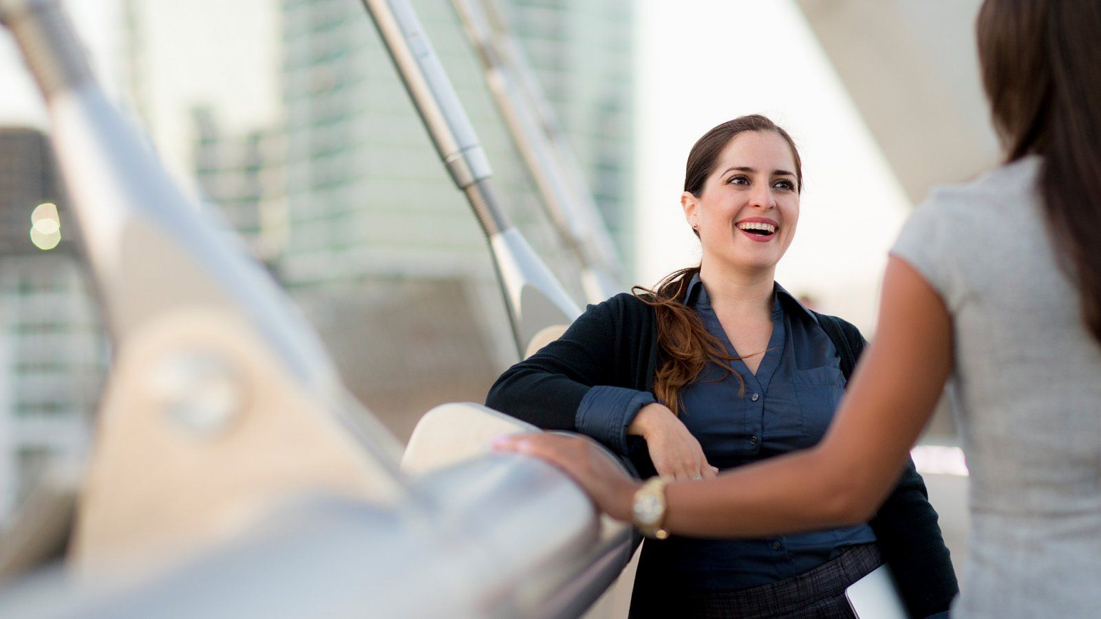 Woman converses with another woman on a pedestrian bridge