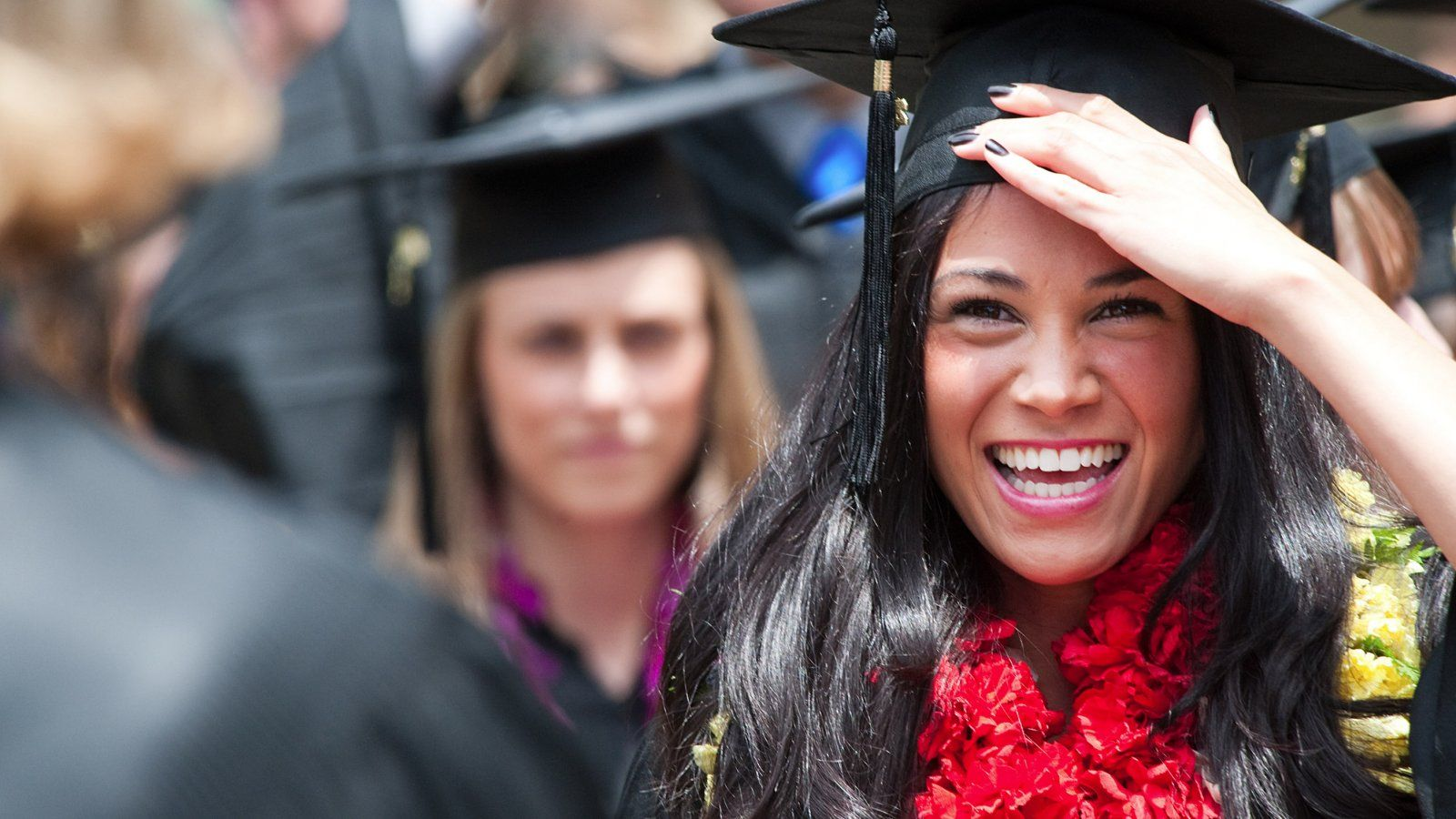 Female student stands out of a crowd at graduation as she holds her cap and smiles in celebration