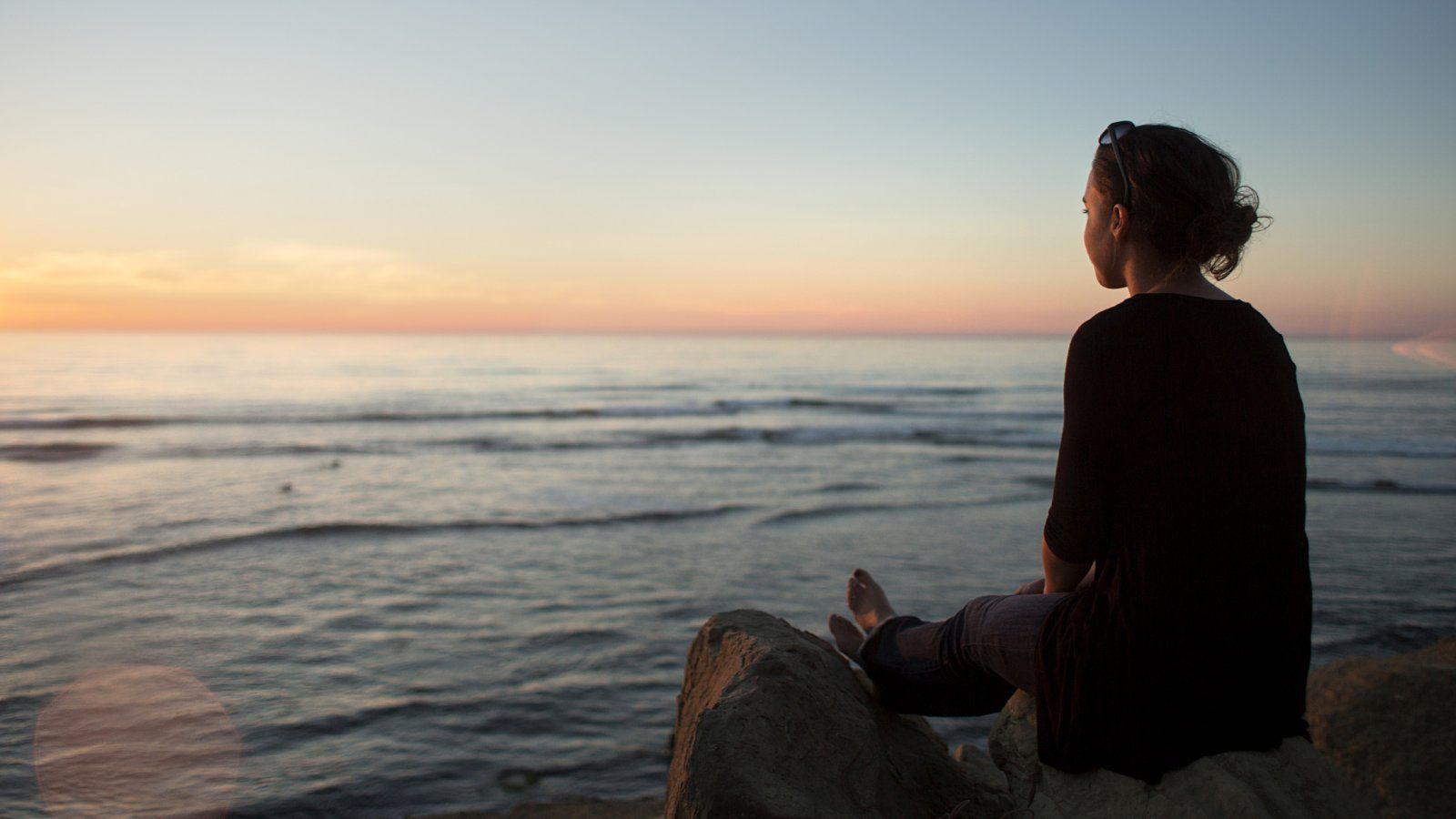 A PLNU student sits on the edge of Sunset Cliffs gazing out on the sunset over the Pacific Ocean