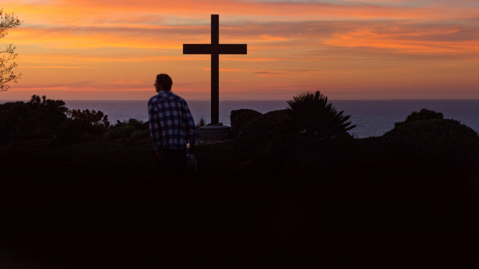 Male student walks past the cross with view of a sunset.