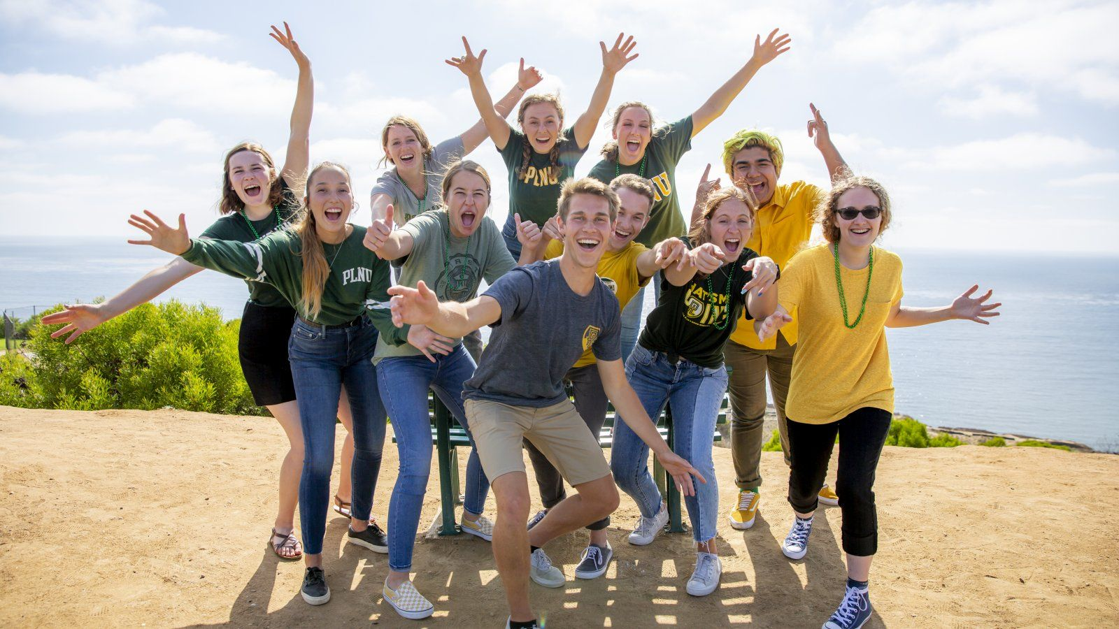 Group of PLNU students cheer and smile