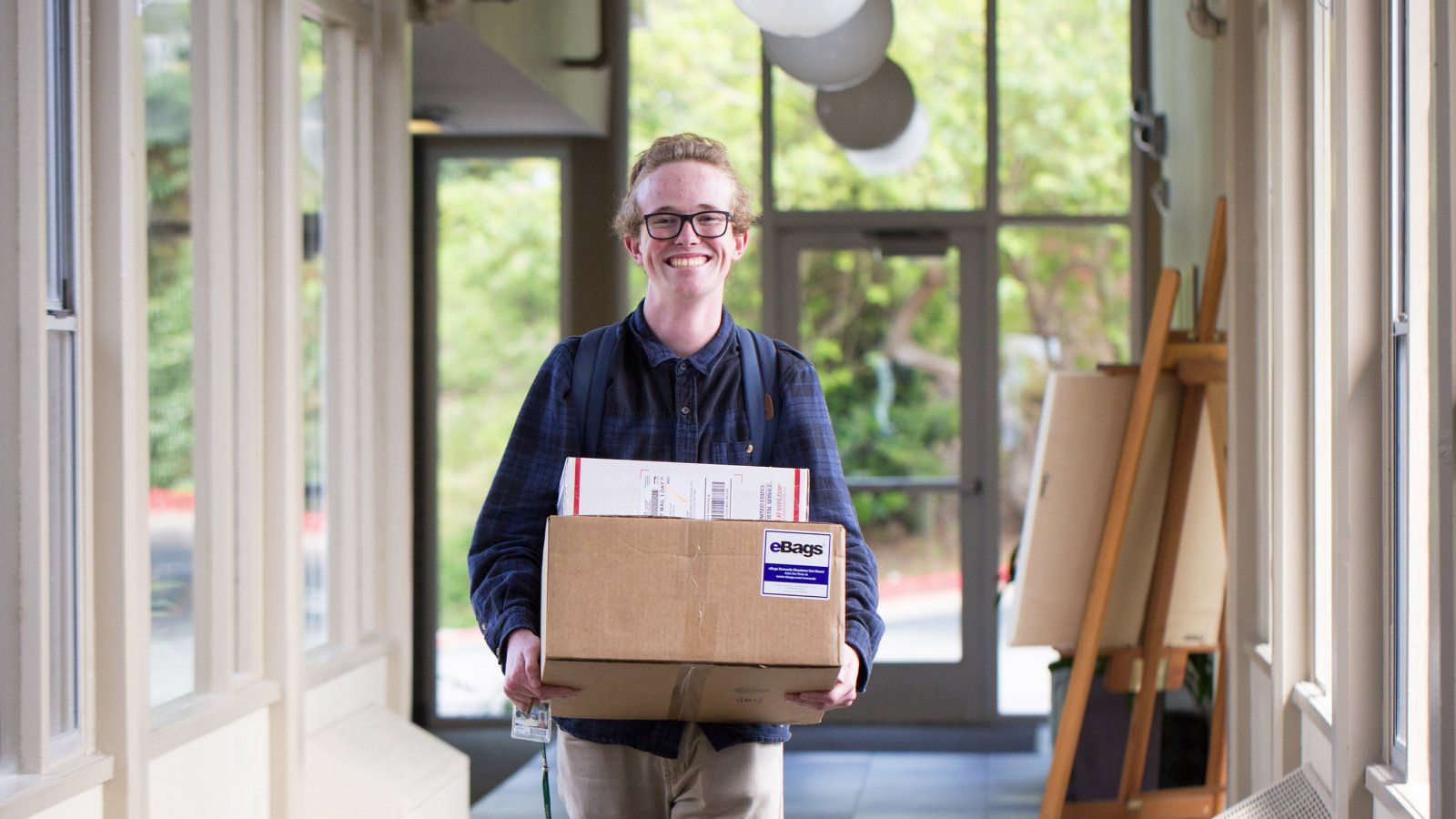 A student carries their mail in a residence hall