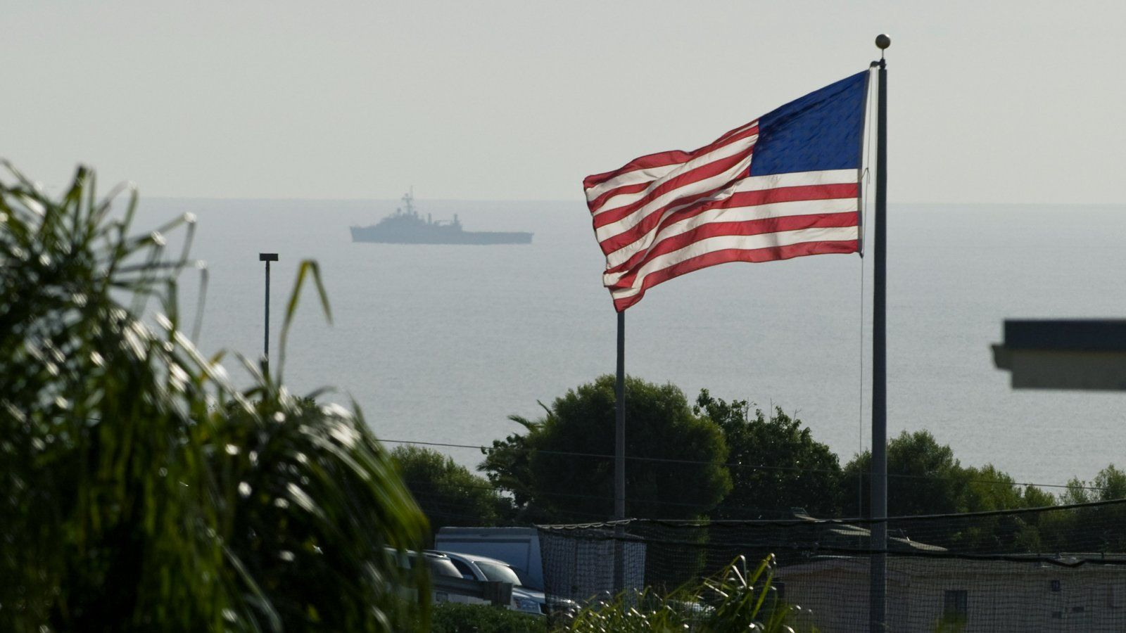 PLNU proudly flies the flag between on campus, while a navy ship maneuvers just off the coast.