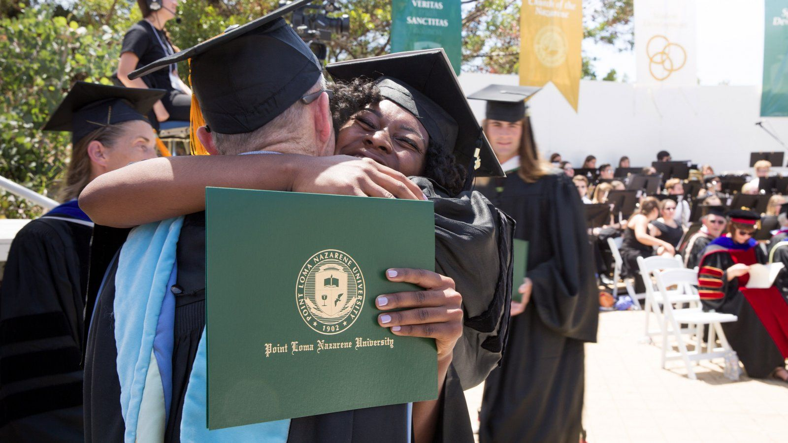 student hugs her professor with diploma in hand, in her cap and gown