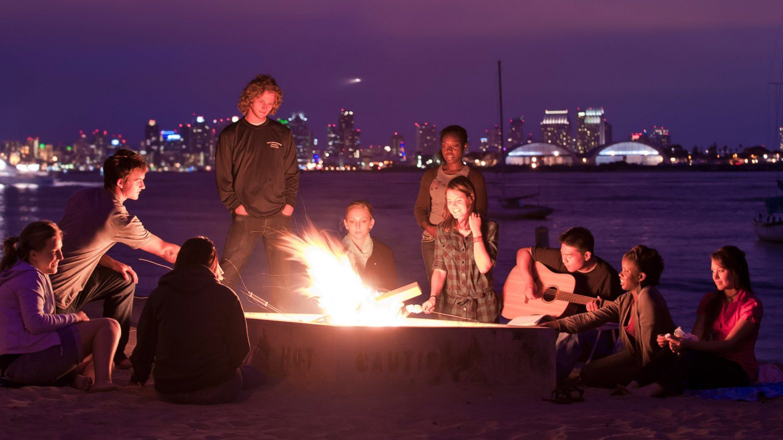 PLNU students gather around a bonfire at Shelter Island.