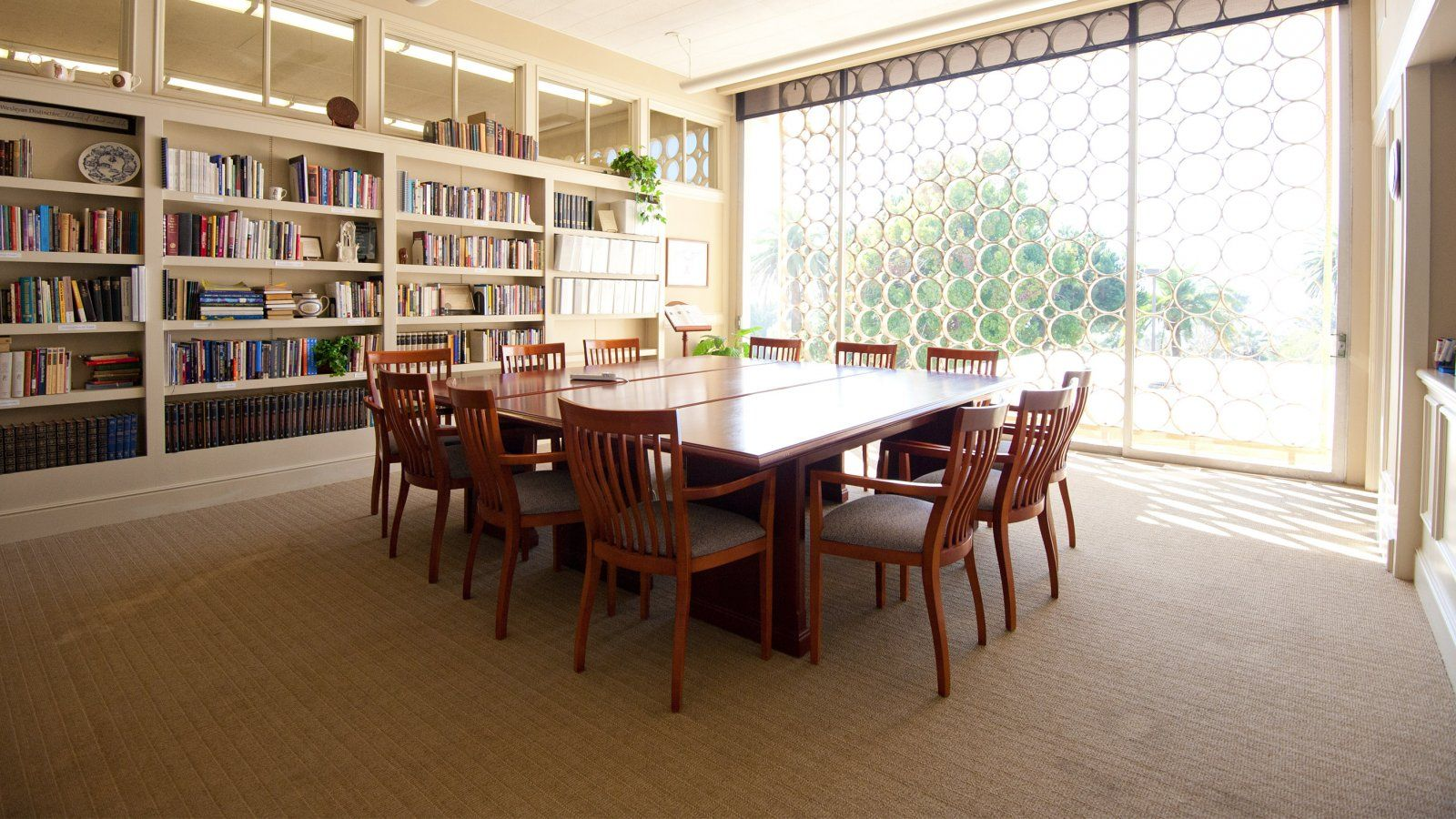 Conference Room with empty square table with a wall of books behind and a wall of windows