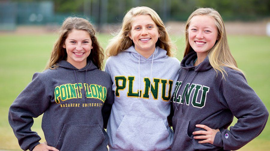 Three PLNU students show their school pride with PLNU sweatshirts as they run on the track.