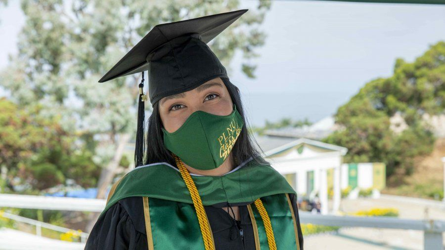 A masked student at PLNU's graduation ceremony