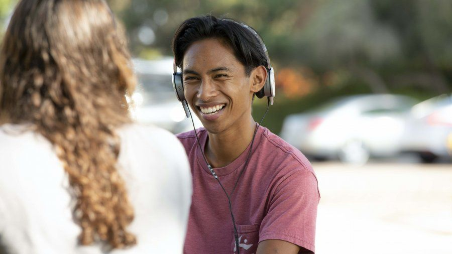 Male student wearing headphones looks up and smiles from his laptop