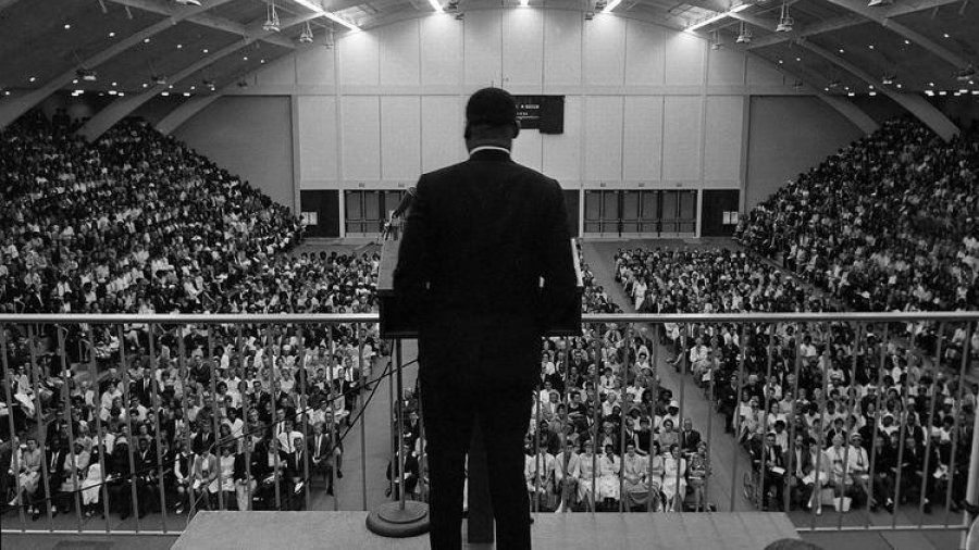 Martin Luther King Jr speaks to a large crowd gathered in Golden Gymnasium.