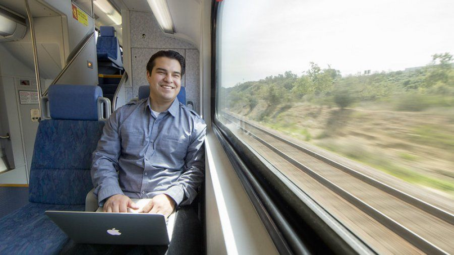 Man smiles and works on a computer while on the train.