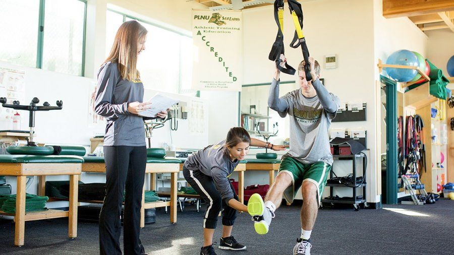 A student athletic trainer helps a PLNU basketball player stretch on equipment in the Athletic Training Center