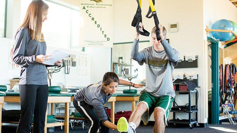 A student athletic trainer helps a basketball player stretch as a professor looks on.