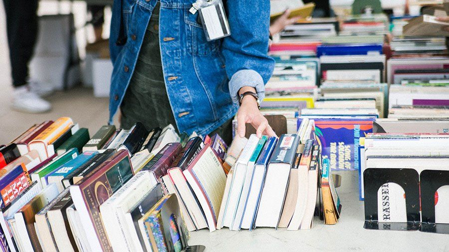 A student browses a number of books during a sale.