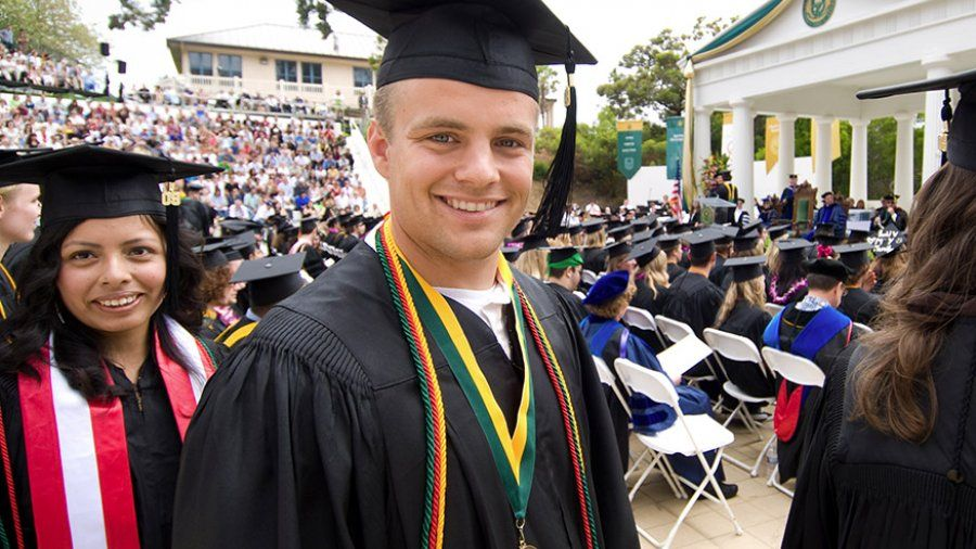 A student smiles as he gets ready to receive his diploma