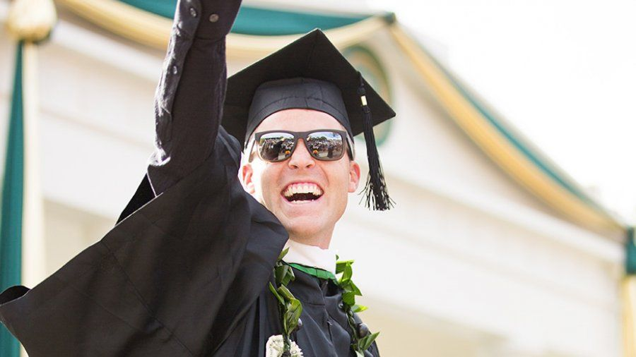 A male student points to the crowd after receiving his diploma