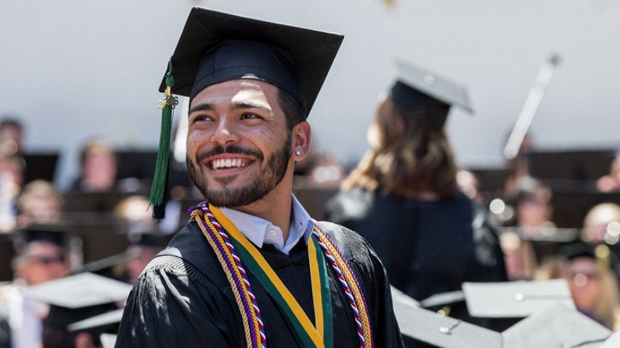 A young man stands smiling and looking into the distance wearing a cap and gown