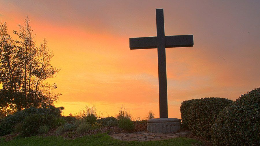 The PLNU campus cross glows during a bright sunset.