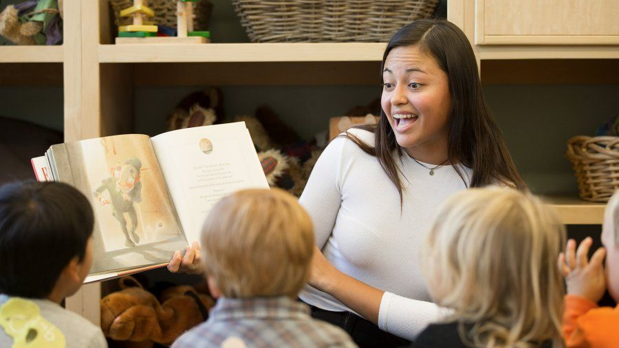 A female college student animatedly reads a children's book to four small children inside