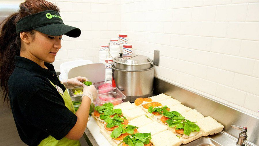 A student worker prepares eight sandwiches for hungry customers.