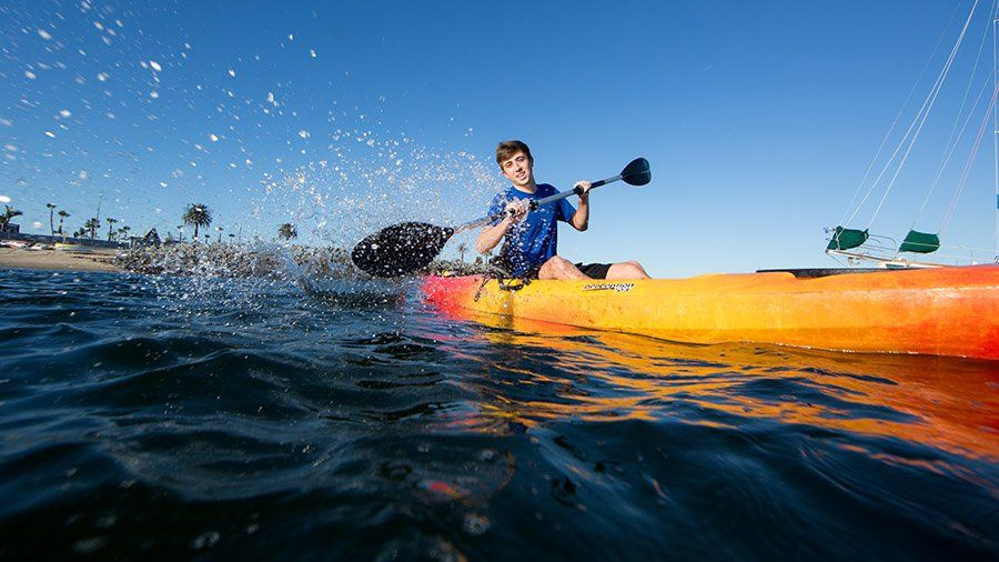 A student splashes water at the camera while paddling a kayak off Shelter Island.