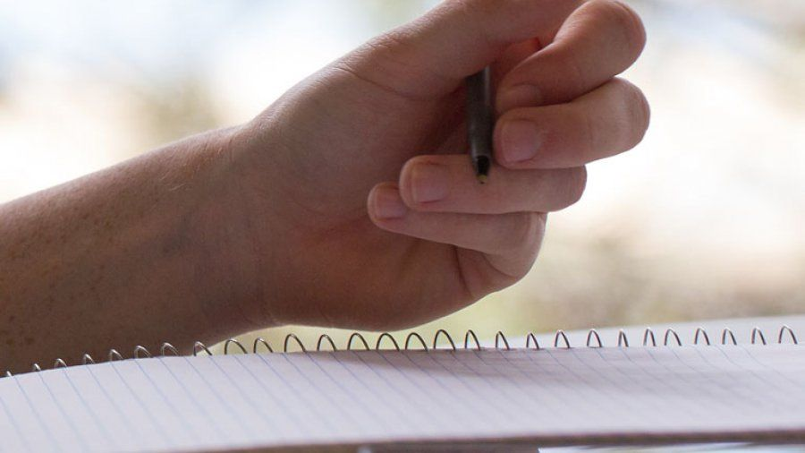 Hand holding a pencil poised to take notes on a spiral-bound notebook