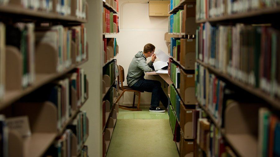 A student looks at his notes and studies on the lower floor of Ryan Library near the bookshelves.