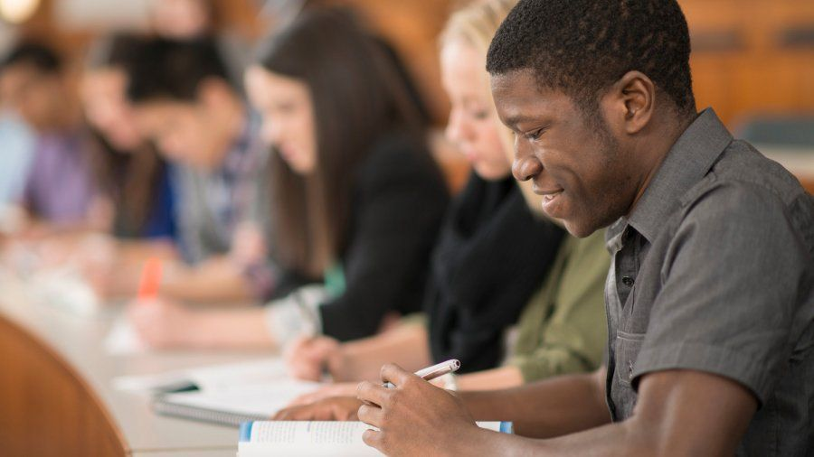 A student looks at a workbook while sitting in a classroom lecture hall.